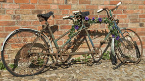 Old Tandem. Old rusty bicycle abandoned by brick wall Royalty Free Stock Photography