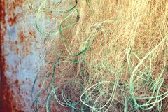 Old tangled fishing net on rusty blue metal background. Toned photo with illumination stock photo