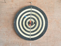 The old target with darts. In the center on the wood wall Stock Photos