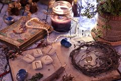 Old tarot cards deck, runes and dried roots with book on table stock image