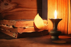 Old tattered book on a wooden table lighted candle and glasses Royalty Free Stock Image