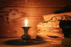 Old tattered book on a wooden table lighted candle and glasses Royalty Free Stock Images