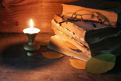 Old tattered book on a wooden table lighted candle and glasses Stock Photos