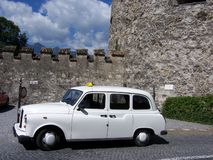 Old Taxi Cab. Old white taxicab at Liechtenstein Castle, Europe, stone wall and parapets royalty free stock images