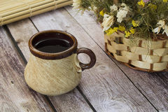 Old tea mug. Tea in an old mug on a light table near burlap Royalty Free Stock Image