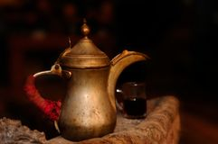 Old metal tea pot. Old tea pot is standing on the edge of fireplace with a tea cup full of tea in the background, Aqaba, Jordan Royalty Free Stock Photos