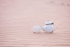 Old teapot and cup in sahara sand dune Royalty Free Stock Photos