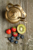 Old teapot with fruits Stock Photos