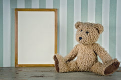 Old teddy bear next to an empty frame Stock Photography