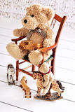 Old teddy bear sitting on the chair with his toys Royalty Free Stock Image
