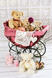 Old teddy bears and toys in vintage baby carriage Stock Photos