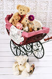 Old teddy bears and toys in vintage baby carriage Stock Photo