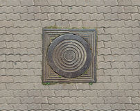 Old teel sewer manhole on the cobblestone road pavement Royalty Free Stock Photo