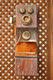 Old telephone. An old wooden phone hanging on the wall Royalty Free Stock Images