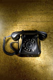 Old telephone. Black, old telephone on a golden surface Royalty Free Stock Photography