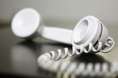 Old Telephone. An old fashioned, vintage style white telephone has the receiver off the hook, and is sitting on a table, with room for text, copyspace.  Shallow Stock Photo