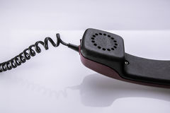 Old telephone handset and cable on white table with reflection Royalty Free Stock Images