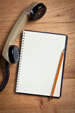 Old telephone handset with notebook Stock Image