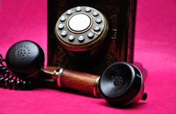 An old telephone. Isolated on a pink background stock photo