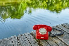 Old telephone in nature. Old telephone on a lakeside pier Stock Images