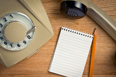 Old telephone with notebook. Top view of old telephone with notebook on wooden table Stock Image