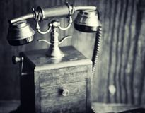 Old telephone and retro book on the desk. The phone of the past. On an old wooden countertop. Long-distance telephone calls of the 19th century.r Stock Photos