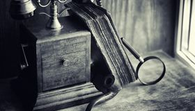Old telephone and retro book on the desk. The phone of the past. On an old wooden countertop. Long-distance telephone calls of the 19th century.r Stock Image