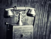 Old telephone and retro book on the desk. The phone of the past. On an old wooden countertop. Long-distance telephone calls of the 19th century.r Royalty Free Stock Image
