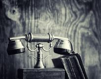 Old telephone and retro book on the desk. The phone of the past. On an old wooden countertop. Long-distance telephone calls of the 19th century.r Stock Images