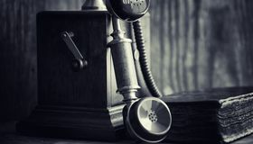 Old telephone and retro book on the desk. The phone of the past. On an old wooden countertop. Long-distance telephone calls of the 19th century.r Royalty Free Stock Images