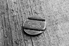Old telephone token. On wood Stock Photography