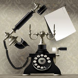 Old telephone on vintage background and a paper sheet with call Stock Photography