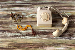 An old telephone on a wooden table. Old coins, antique phone and beads on a wooden table close-up stock images