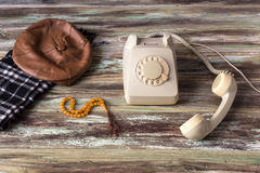 An old telephone on a wooden table. Men`s cap and scarf, antique phone and beads on a wooden table close-up royalty free stock photography