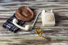 An old telephone on a wooden table. Men`s cap and scarf, antique phone and beads on a wooden table close-up stock photos