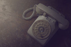 Old telephone on wooden table. Vintage color royalty free stock image