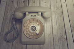 Old telephone on wooden table. Vintage color royalty free stock images