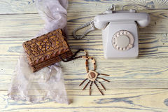 An old telephone on a wooden table. Women wooden necklace, casket and antique phone on a wooden table close-up royalty free stock image