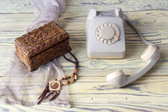 An old telephone on a wooden table. Women wooden necklace, casket and antique phone on a wooden table close-up stock photos