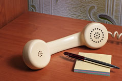 Old telepnone handset with notebook on wooden table.  Royalty Free Stock Images