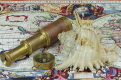 Old telescope, compass, seashell and vintage map of the world. Stock Photography