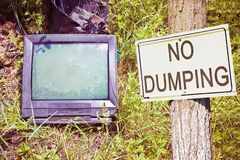 Old television CRT Cathode ray tube abandoned in nature with No Dumping text - concept image with copy space.  royalty free stock photo