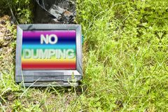 Old television CRT Cathode ray tube abandoned in nature with. `No Dumping ` text - concept image with copy space royalty free stock images