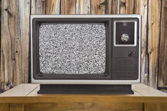 Old Television with Static Screen and Rustic Wood Wall Stock Image