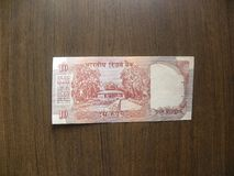 Old ten Rupees India note. Reverse of red color old 10 rupees India banknote with museum building and trees portrait kept on wooden table stock photos