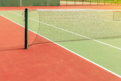 Old tennis court. Oldgreen tennis court with net pole and net, with sun light Stock Image