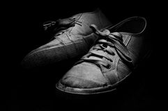 Old Tennis Shoes on black background. Old and used white tennis shoes on black background Royalty Free Stock Photo