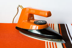 The old terracotta color iron with a striped cord stands on the Stock Images
