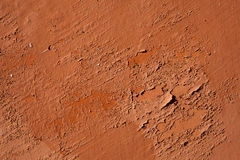 Old terracotta painted stucco wall with chipped paint. Backgroun Stock Images
