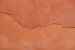 Old terracotta painted stucco wall with cracked plaster. Backgro Royalty Free Stock Photos